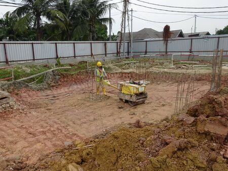 roller compactor: SELANGOR, MALAYSIA  SEPTEMBER 25, 2015: Construction workers using baby roller compactor to compact soil at the construction site on September 15, 2015.
