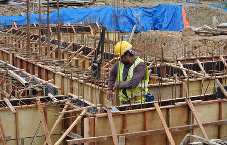 fabricating: SELANGOR, MALAYSIA  SEPTEMBER 22, 2015: Group of construction workers fabricating ground beam timber formwork at construction site in Selangor, Malaysia on September 22, 2015.