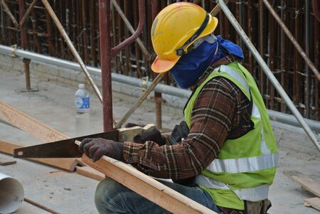 carves: MALACCA, MALAYSIA  OCTOBER 21, 2015: Carpenter sawing timber at the construction site in Malacca, Malaysia on October 21, 2015 Editorial