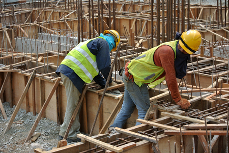 fabricating: MALACCA, MALAYSIA  SEPTEMBER 22, 2015: Group of construction workers fabricating ground beam steel reinforcement bar at the construction site in Malacca, Malaysia on September 22, 2015.