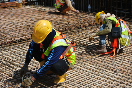 fabricating: MALACCA, MALAYSIA  NOVEMBER 14, 2015: A construction workers fabricating floor slab reinforcement bar at the construction site in Malacca, Malaysia on November 14, 2015. Editorial