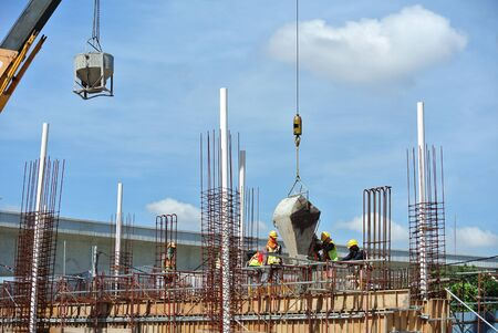 Group of construction workers pouring wet concrete into floor slab at the construction site