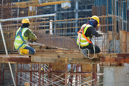 Construction workers fabricating high level beam steel reinforcement bar at the construction site in Malacca, Malaysia