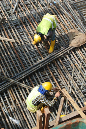 fabricating: MALACCA, MALAYSIA  SEPTEMBER 22, 2015: Group of construction workers fabricating steel reinforcement bar at the construction site in Malacca, Malaysia on September 22, 2015. Editorial