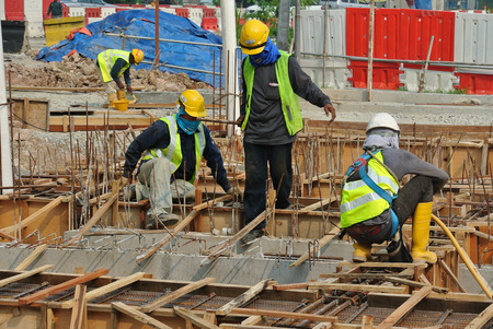 fabricating: SELANGOR, MALAYSIA  OCTOBER 17, 2015: Group of construction workers fabricating ground beam timber form work at construction site in Selangor, Malaysia on October 17, 2015.