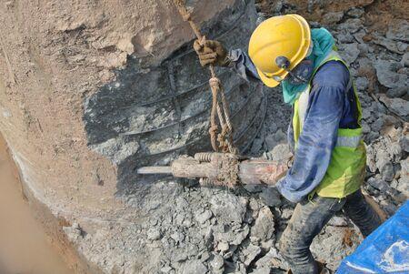 confine: Construction worker using mobile concrete hacker to hack concrete pile at the construction site Stock Photo