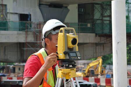 topografo: Surveyor utilizando equipos encuesta en el sitio de construcci�n