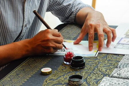 wrote: A man wrote an Arab calligraphy words on piece of paper.