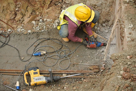 making hole: Construction workers make holes at the building pile cap using mobile drilling machine.