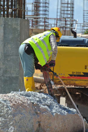 heavy duty: JOHOR, MALAYSIA -JANUARY 13, 2015: A construction workers cutting foundation pile using hacking method at the construction site. He using the heavy duty mobile hacker machine.