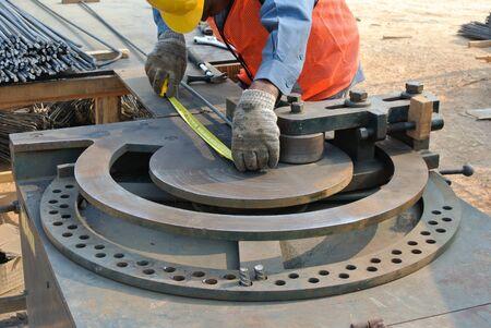 Bauarbeiter bei der Bewehrungsstab Arbeits Hof in der Baustelle zu biegen. Standard-Bild
