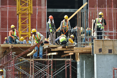Construction workers wearing safety harness and adequate safety gear while working at high level at the construction site in Seremban, Malaysia. Editorial