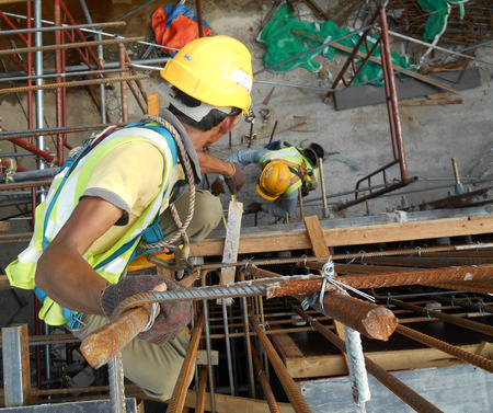 safety harness: Construction workers wearing safety harness and adequate safety gear while working at high level at the construction site in Seremban, Malaysia. Stock Photo