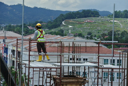 PERAK, MALAYSIA -JULY 18, 2016: Construction workers wearing safety harness and installing scaffolding at high level in the construction site.