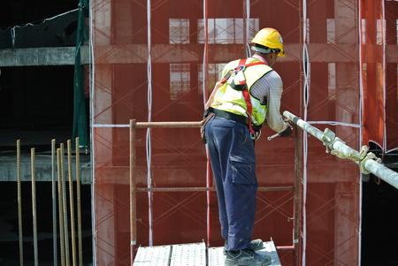 Perak, Malasia-Julio 18, 2016: Los trabajadores de construcción que llevaba arnés de seguridad y la instalación de andamios a alto nivel en el sitio de construcción. Editorial