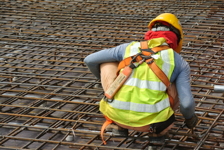reinforcement: MALACCA, MALAYSIA -JUNE 27, 2016: Construction workers fabricating steel reinforcement bar at the construction site in Malacca, Malaysia. The reinforcement bar was ties together using tiny wire.