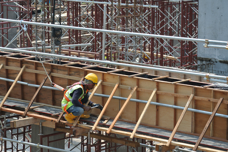 MALACCA, MALAYSIA -MARCH 25, 2016: Construction workers fabricating beam and column timber form work and reinforcement bar at the construction site in Malacca, Malaysia.