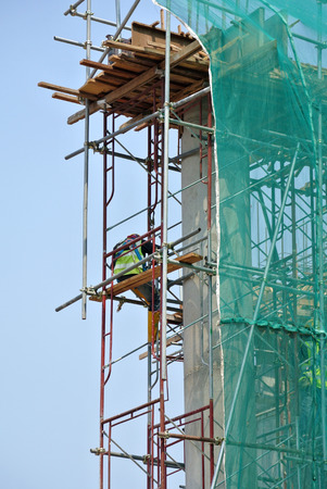 SELANGOR, MALAYSIA -APRIL 05, 2016: Construction workers wearing safety harness and installing scaffolding at high level in the construction site in Selangor, Malaysia. Editorial