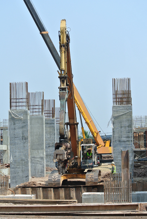 SELANGOR, MALAYSIA –MARCH 15, 2016: Sheet pile cofferdam driven machine at the construction site. The machine drove the sheet pile to the earth using vibrated hydraulic arm. Workers control.