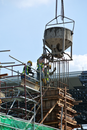 concrete form: JOHOR, MALAYSIA -MARCH 13, 2016: A group of construction workers pouring concrete using concrete bucket into the column form work at the construction site. Editorial