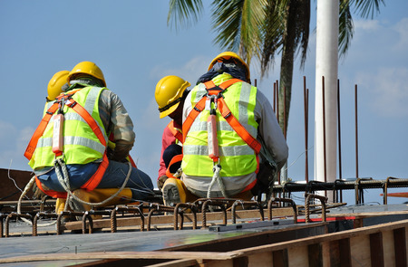 MALACCA, MALAYSIA -MARCH 29, 2016: Construction workers fabricating steel reinforcement bar at the construction site in Malacca, Malaysia. The reinforcement bar was ties together using tiny wire.