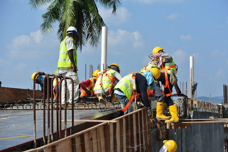 plywood: MALACCA, MALAYSIA -MARCH 25, 2016: Construction workers fabricating beam and column timber form work and reinforcement bar at the construction site in Malacca, Malaysia.