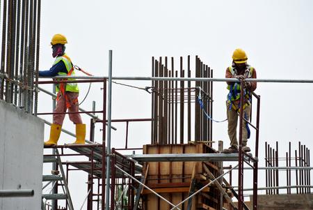 Selangor, Malaysia ABRIL 05, 2016: Los trabajadores de construcción que llevaba arnés de seguridad y la instalación de andamios a alto nivel en el sitio de construcción en Selangor, Malasia.
