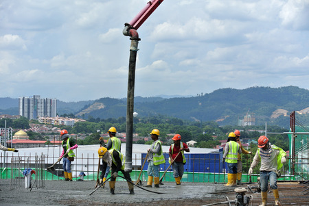 PERAK, MALAYSIA -SEPTEMBER 05, 2016: Construction workers pouring wet concrete to floor slab form work using hose from the elephant crane or concrete pump crane at the construction site.