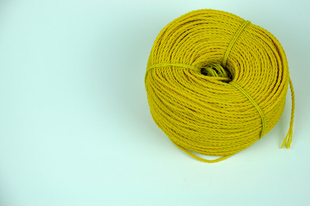 A roll of yellow nylon rope with on white background.