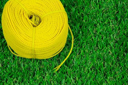 A roll of yellow nylon rope with on artificial grass background.