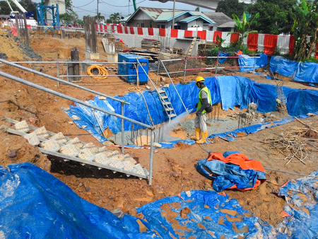 Construction workers spraying the anti termite chemical treatment to the soil at the construction site.