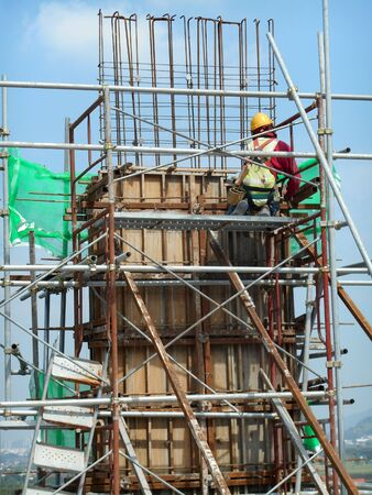 Construction workers fabricating timber form work at the construction site in Johor, Malaysia. The form work was mainly made from timber and plywood.