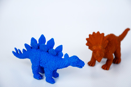 Triceratops and Stegosaurus dinosaur model made from brown and blue rubber isolated on white background.