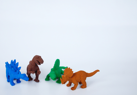 Triceratops, Stegosaurus, Spinosaurus and Tyrannosaurus dinosaur model made from multicolor rubber isolated on white background.