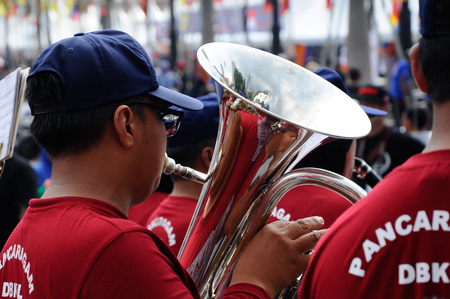 KUALA LUMPUR, MALAYSIA -FEBRUARY 22, 2017: Brass band player is playing a musical instrument while guided by musical notes.