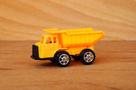 Small heavy construction machine toy, lorry. Made of plastic isolated on a wood grain texture background.