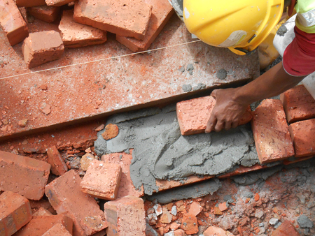 KUALA LUMPUR, MALAYSIA -JULY 14, 2016: Construction workers laying clay bricks at the construction site to form a wall. The brick stick together using the cement mortar. Foto de archivo