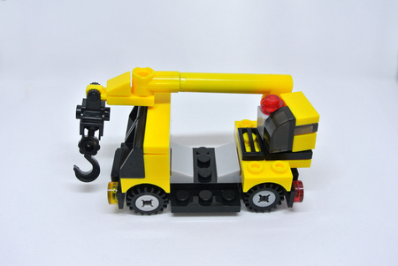 Selective focused miniature of mobile crane machine made from plastic block and isolated on white background.