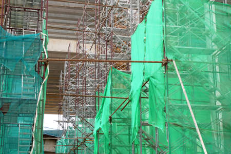 SHAH ALAM, MALAYSIA -AUGUST 8, 2020: Temporary staircase and falsework are used as a temporary support during construction. It is wrapped with safety netting for safety purposes. Installed by worker