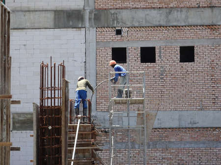MALACCA, MALAYSIA -MARCH 12, 2020: Construction workers working at height at the construction site. They are supplied with harnesses and other safety equipment to prevent them from having an accident.