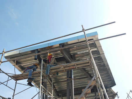 MALACCA, MALAYSIA -MARCH 14, 2020: Construction workers working at height at the construction site. They are supplied with harnesses and other safety equipment to prevent them from having an accident.