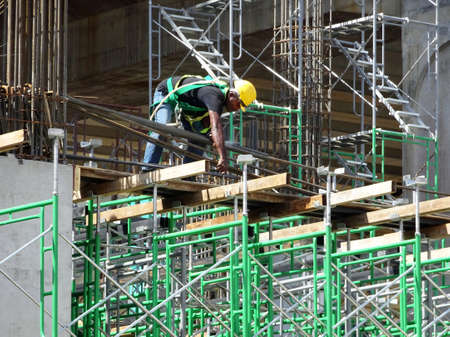 MALACCA, MALAYSIA -MARCH 2, 2020: Construction workers working at height install reinforcement bars at the construction site. They are supplied with harnesses and other safety equipment.