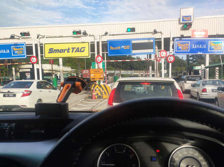 SEREMBAN, MALAYSIA -AUGUST, 2020: Vehicles entering highway toll canopy in Malaysia. Vehicles that use the expressway through a toll plaza and make payments each time they enter and exit.