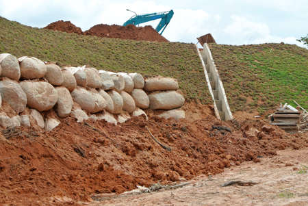 Stone boulders are stacked on the ground and used as retaining walls. It acts to resist soil erosion caused by rain.