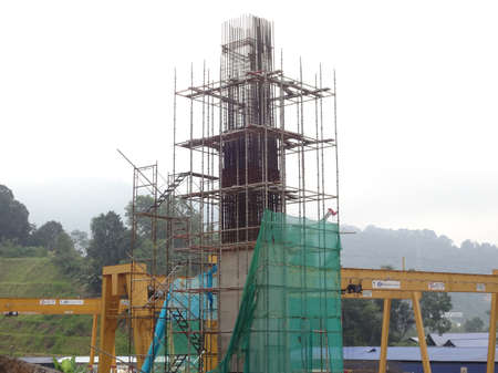 SHAH ALAM, MALAYSIA -AUGUST 6, 2020: Temporary staircase and scaffolding are used in the construction of high concrete columns. Scaffolding is wrapped with safety netting for safety purposes. Installe