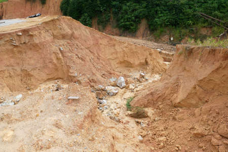 Erosion at ground and slopes is caused by rainfall. The soil structure is weak and there is a landslide. Safety measure has been taken in some area.