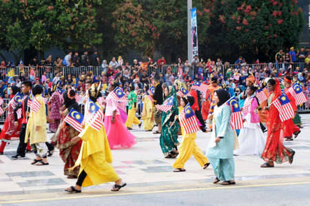 PUTRAJAYA, MALAYSIA -AUGUST 31, 2019: Teenagers wearing Malaysian ethnics and tribes traditional cloth marching on the road while holding Malaysian state flags. Redakční