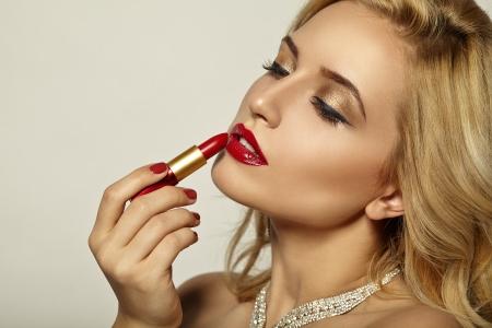Girl paints her lips red lipstick  Beautiful portrait  photo
