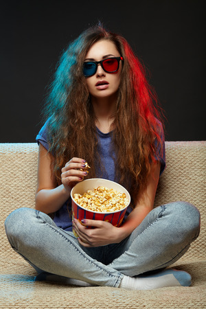 Beautiful girl watching movie with 3d glasses and eating