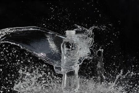 Fresh water splashing out of bottle, black background photo